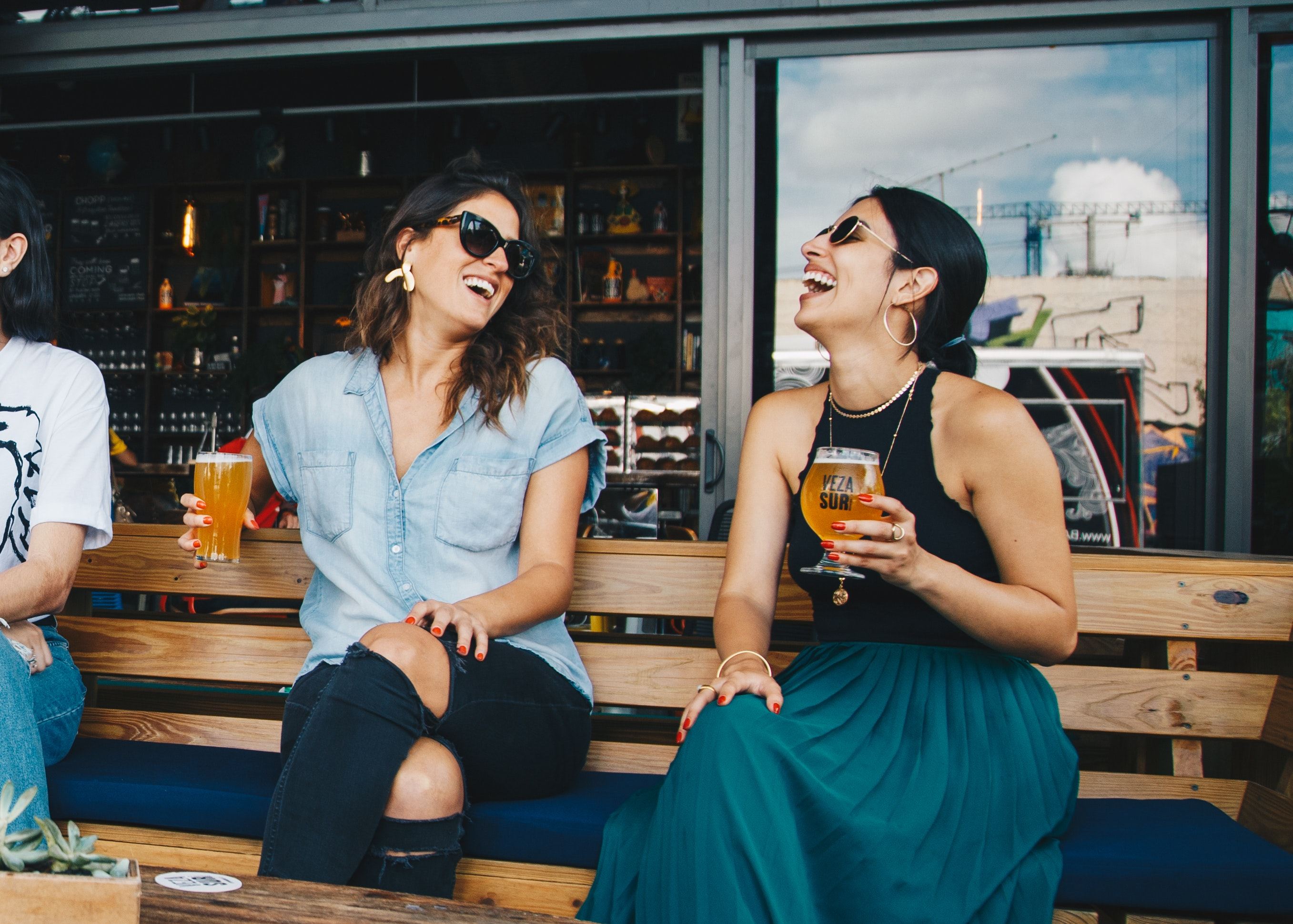 two women sitting on a patio with beers and laughing together how to be happy and healthy